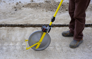 Surveyor with measuring wheel (odometer) detects the length of an excavation of minitrench