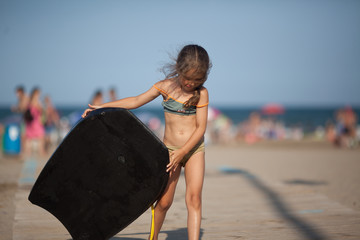 Little girl on the beach with a surfboard