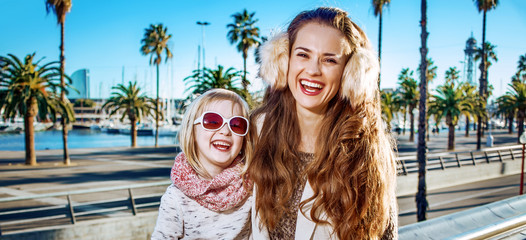 mother and daughter travellers on embankment in Barcelona