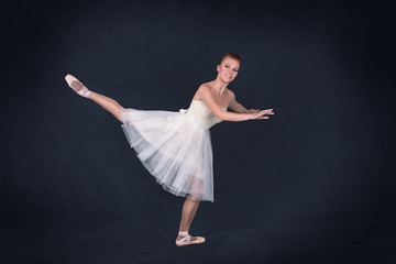 the ballerina in pointes and a white dress dances on a dark background