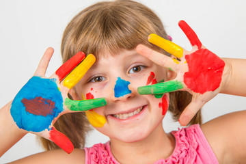 smiling little girl with hands painted in colorful paints