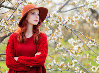girl in red clothes in blossom cherry garden