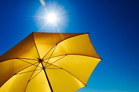 Gelber Sonnenschirm mit strahlend heller Sonne und blauem Himmel