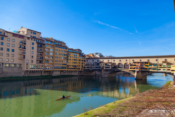 Arno river with unknown man on kayak, houses and old Ponte Vecchio bridge, Florence, Tuscany, Italy