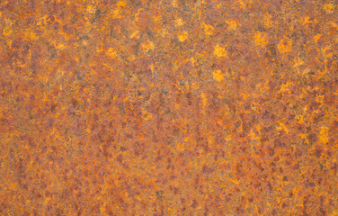 Rusty yellow metal surface. Saturated orange, red, grunge rusty metal texture background. Corroded metal plate wallpaper. Typical corrosion on damaged metal fence. Close-up of rusty old steel sheet.