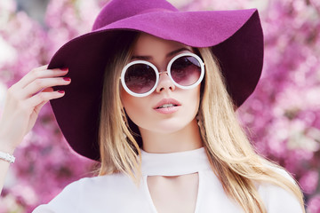 Outdoor close up portrait of young beautiful girl wearing stylish round sunglasses, trendy violet hat, white shirt, posing in street. Pink blooming trees on background. Spring fashion concept.