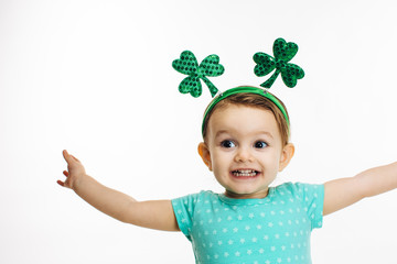 Excited child with arms out and St.Patrick's Day clover head decoration