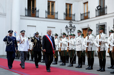 Chile's President Sebastian Pinera walks past honour guard at La Moneda Presidential Palace in Santiago