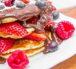 dish with pancakes and strawberry,raspberry and blueberry and chocolate