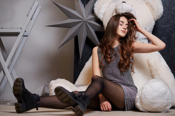 Young pretty woman having fun,holding big soft teddy bear. Beautiful girl hugging big teddy bear soft toy. Fashion girl alone with bear toy in a room sits on the floor. Party. Teen girl. Hipster.