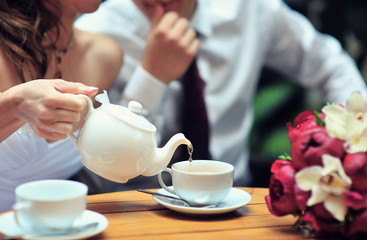 A newlywed couple drinking hot coffee or tea with sweet dessert in warm cozy cafe with wedding bouquet on the table. Atmoshere of happiness of new family and love tenderness