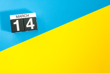 March 14th. Day 14 of march month, calendar on blue and yellow background flat lay, top view. Spring time. Empty space for text