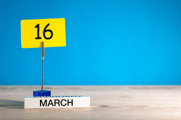 March 16th. Day 16 of march month, calendar on little tag at blue background. Spring time. Empty space for text, mockup