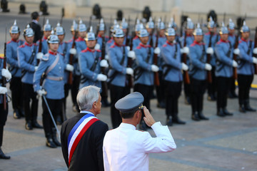 Chile's President Sebastian Pinera stands near the honour guard at La Moneda Presidential Palace in Santiago, Chile