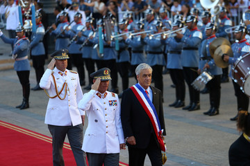 Chile's President Sebastian Pinera walks past the honour guard at La Moneda Presidential Palace in Santiago, Chile