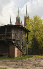 All of old Poland in one photo. Old wooden barn against the background of a medieval cathedral. Beautiful Polish autumn. Overcast.