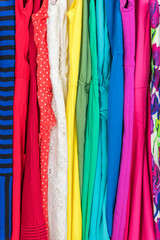 Clothing closet many colorful dresses, variety of fabric and patterns for summer fashion . Women's clothes selection closeup of texture in pink, red, green, blue dress, with stripes, lace, polka dots.