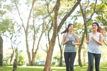 Young Asian woman friends running in the park