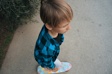 Blond boy in blue shirt on a skateboard