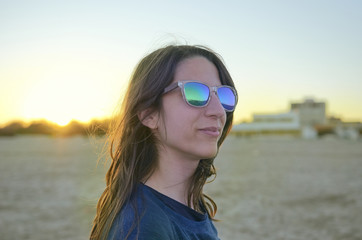 Portrait of young woman with sunglasses at sunset