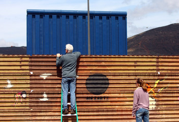 A tourist looks on over a prototype for U.S. President Donald Trump's border wall with Mexico behind the current border fence,in Tijuana