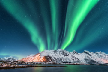 Foto auf Leinwand Nordlicht Aurora borealis. Lofoten islands, Norway. Aurora. Green northern lights. Starry sky with polar lights. Night winter landscape with aurora, sea with sky reflection and snowy mountains.Nature background
