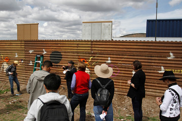 Tourist stand near prototypes for U.S. President Donald Trump's border wall with Mexico behind the current border fence, in Tijuana