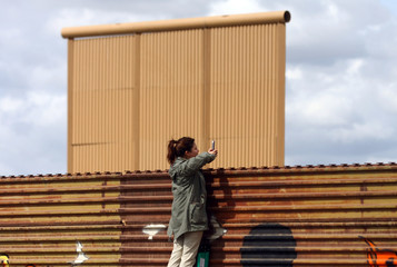 A tourist  takes pictrures at a prototype for U.S. President Donald Trump's border wall with Mexico behind the current border fence,in Tijuana
