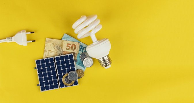 Solar panel with varied values of Brazilian money, power plug and lamp isolated in yellow background.