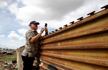A tourist takes pictures of prototypes of U.S. President Donald Trump's border wall with Mexico behind the current border fence in this picture taken from the Mexican side of the border in Tijuana