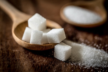 Close up the sugar cubes and cane in wooden spoon on the table Wall mural
