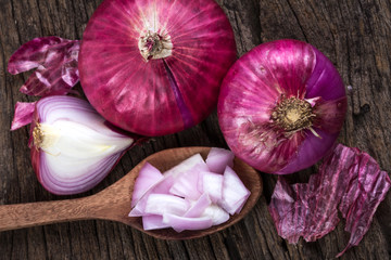 Close up of the sliced red onion and whole bulb onion on a wooden background
