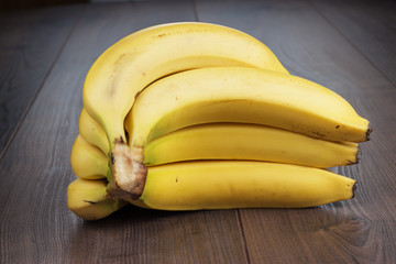 fresh bananas on the brown wooden background