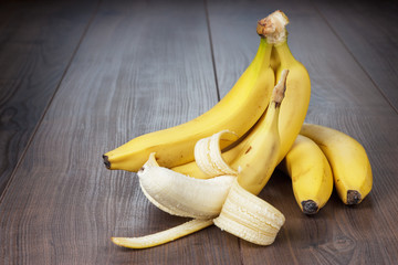 fresh peeled banana on the brown wooden background