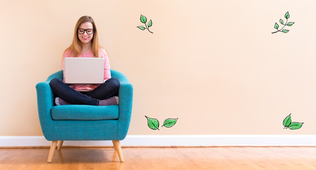 Green Leaves with young woman using her laptop in a chair