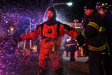 A FDNY rescue diver is hosed off with fresh water after pulling victims from a submerged helicopter after it crashed into the East River in New York