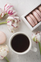 Spring morning concept. Flat-lay of cup of coffee with flowers and macarons, top view with space for your text