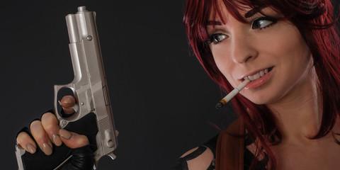 Beautiful redhead woman with gun against dark background