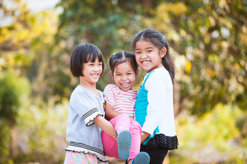 Two happy asian children carrying her sister and they are playing together with fun in the park