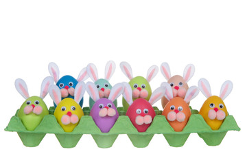 Colorful decorated Easter Eggs with bunny faces and ears sitting in an egg carton isolated on white backgound. Fun easter concept.