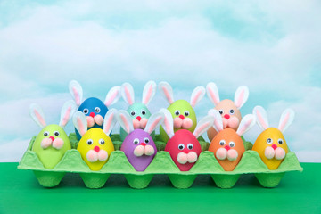 Colorful decorated Easter Eggs with bunny faces and ears sitting in an egg carton on green table, vintage sky background. Fun easter concept.