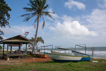 Fisherman's boats of  at the beach and Malaysia flag waving above of hut's roof