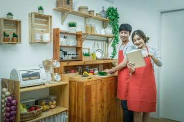 Happy Asian Lover or couple cooking and following the tutorial in technology tablet with happiness action in the kitchen room at the modern house, Couple and life style concept.