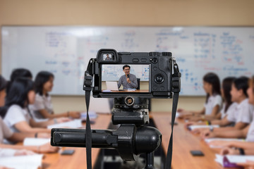 Professional digital Mirrorless camera on the tripod recording video blog of Asian teacher in the classroom, Camera for photographer or Video and Technology Live Streaming concept,education concept