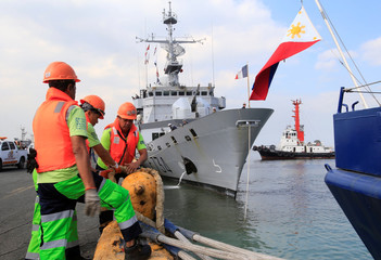 Filipino port workers tie the mooring rope from the docking French Navy ship Vendemiaire (F734), a Floreal-classlight surveillance frigate of the French Marine Nationale upon its arrival for a five-days goodwill visit at a port in Metro Manila