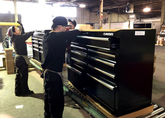Workers install wooden tops onto toolboxes on the assembly line at Metal Box International in Franklin Park