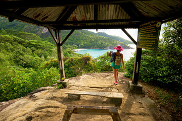 Anse major trail,  a woman hiking on nature trail of Mahe, in order to view anse major beach Seychelles