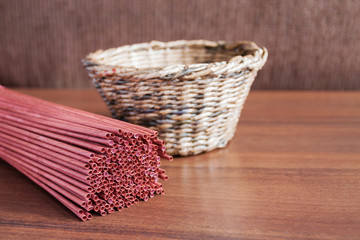 Red newspaper tubules for newspaper weaving and handmade basket on the background. Closeup, selective focus.