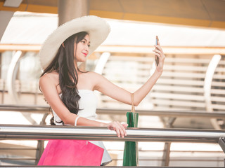 Beautiful young woman making self-portrait by smart phone after enjoying in shopping. Consumerism and lifestyle concept
