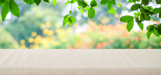 Empty table with brown linen tablecloth over blurred park nature background, for product display montage, spring and summer
